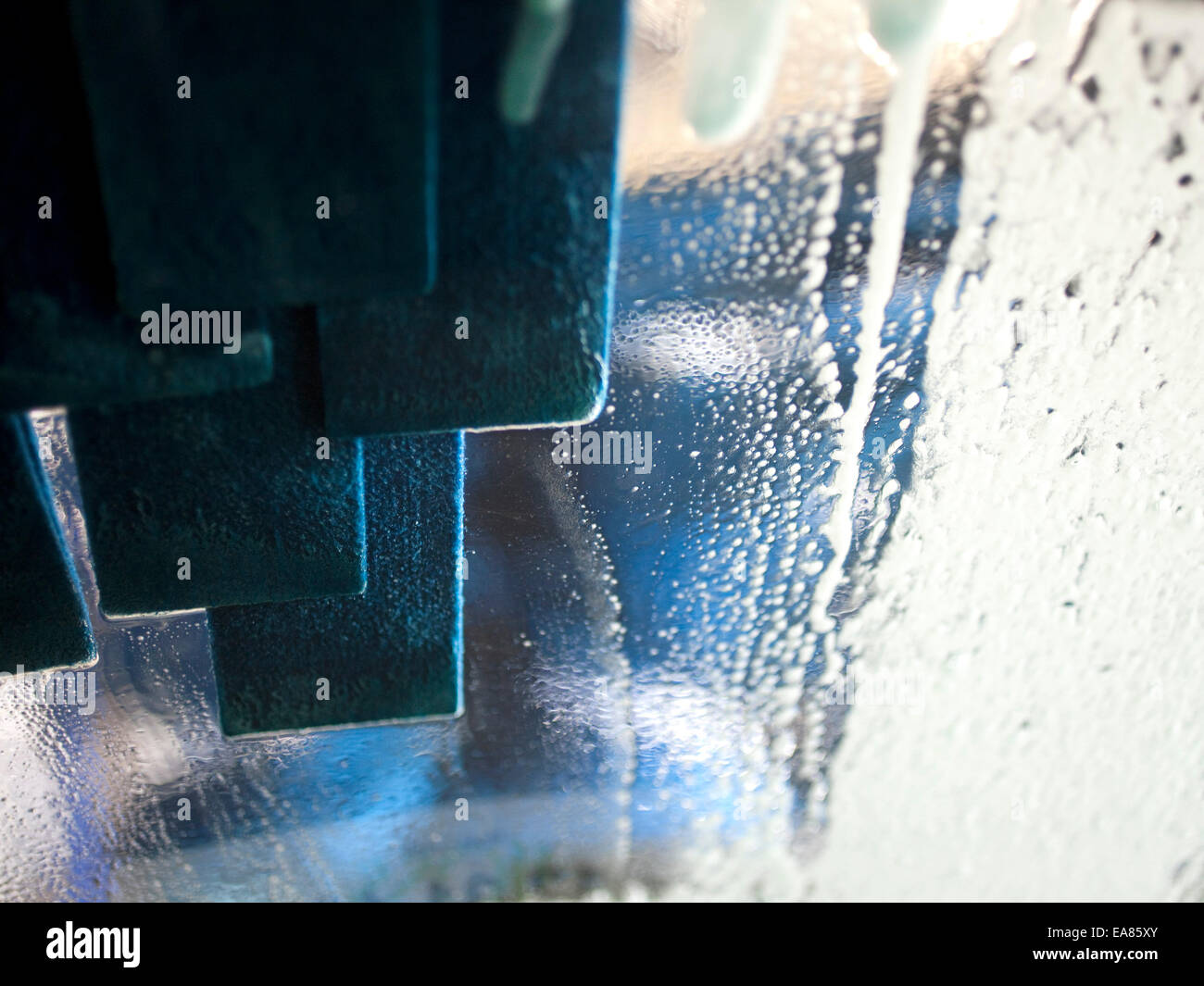 windshield of car being cleaned while going through car wash. - Stock Image