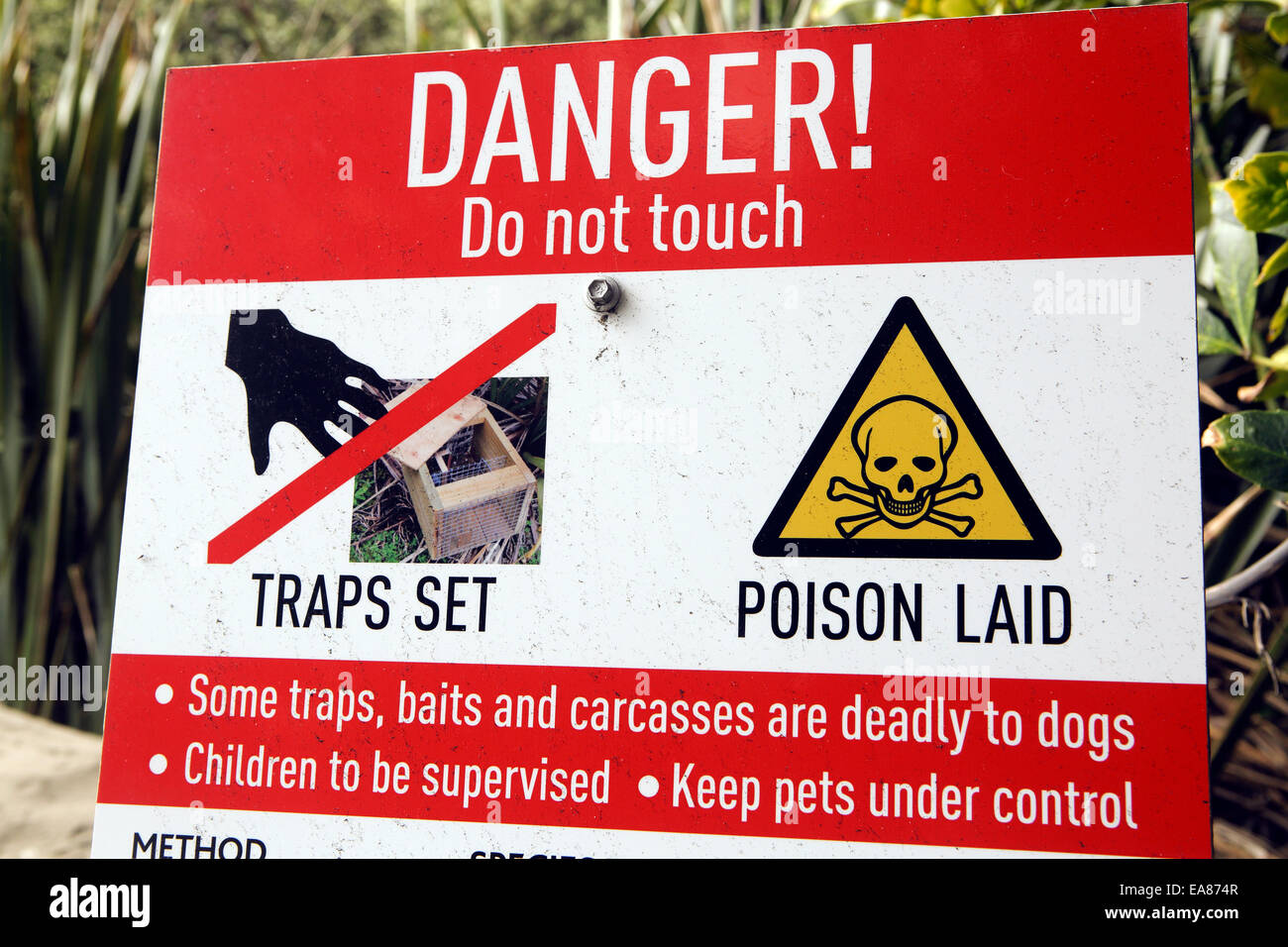 Sign in New Zealand forest warning of traps and poison set for pests in the protection of native bird species - Stock Image