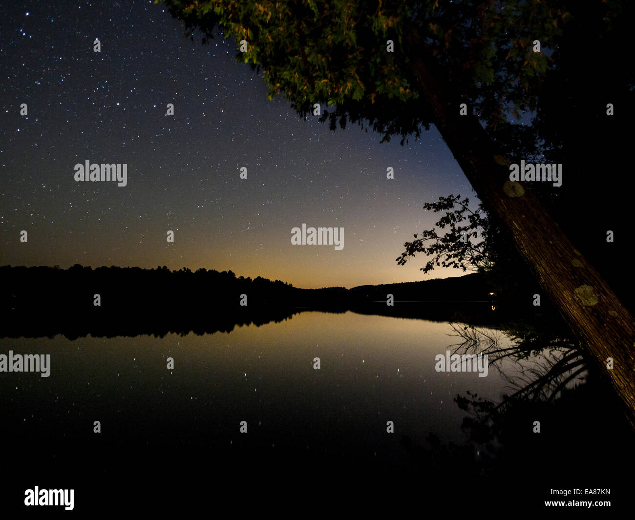 Ottawa Glow on a Starry Night. Stars reflect in a glassy lake in this long exposure. The yellow glow of distant - Stock Image