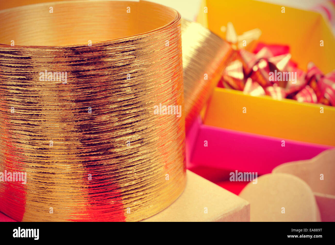 golden ribbon, boxes and ribbon bows of different colors to prepare gifts, with a retro effect - Stock Image