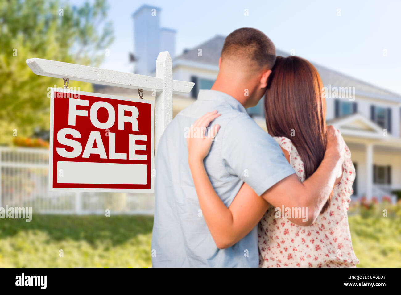 For Sale Real Estate Sign and Affectionate Military Couple Looking at Nice New House. - Stock Image