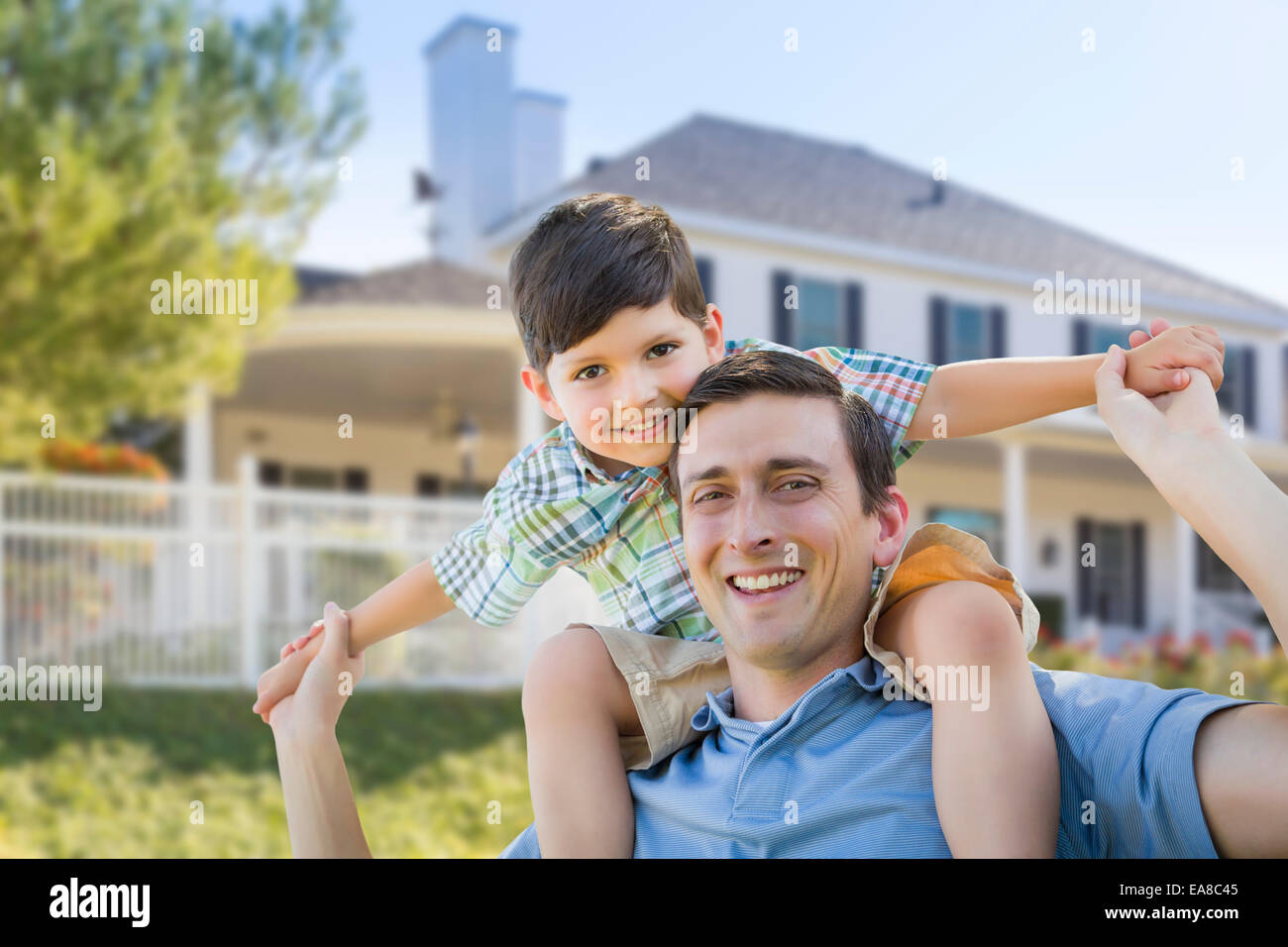 Mixed Race Father and Son Playing Piggyback in Front of Their House. - Stock Image