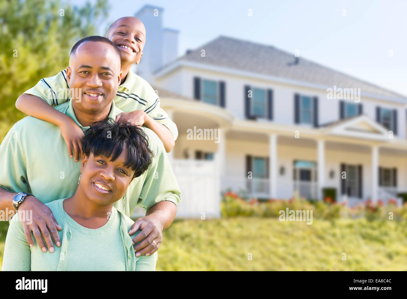 Happy Attractive African American Family in Front of Beautiful House. - Stock Image