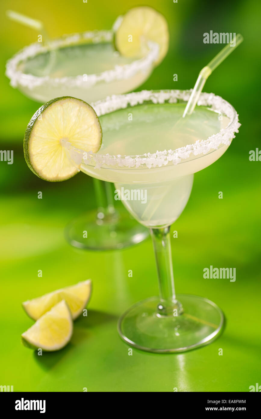 Two tequila margaritas with tequila, lime, and salt against a vibrant abstract green background. - Stock Image