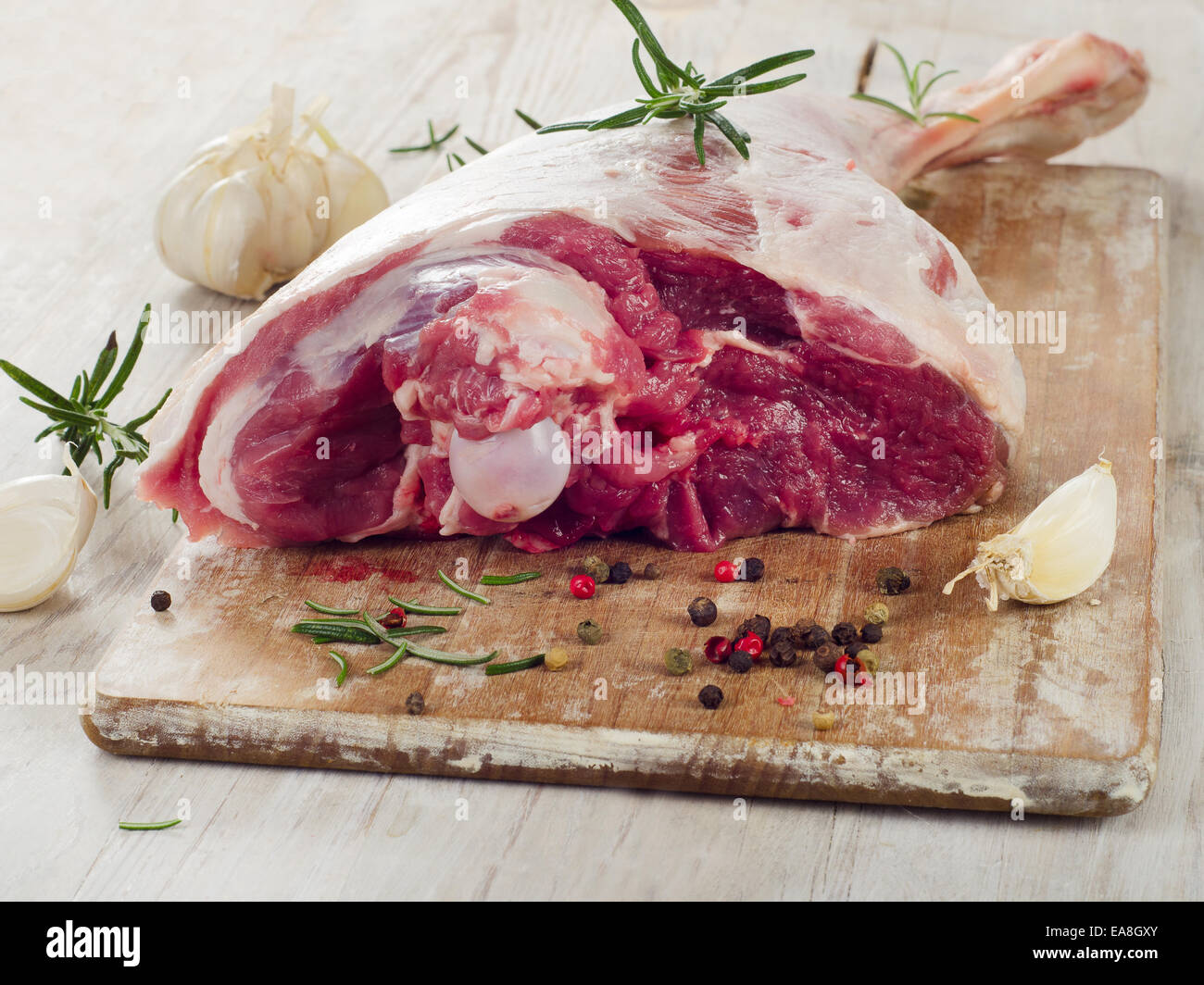 Raw lamb leg on a wooden table. - Stock Image