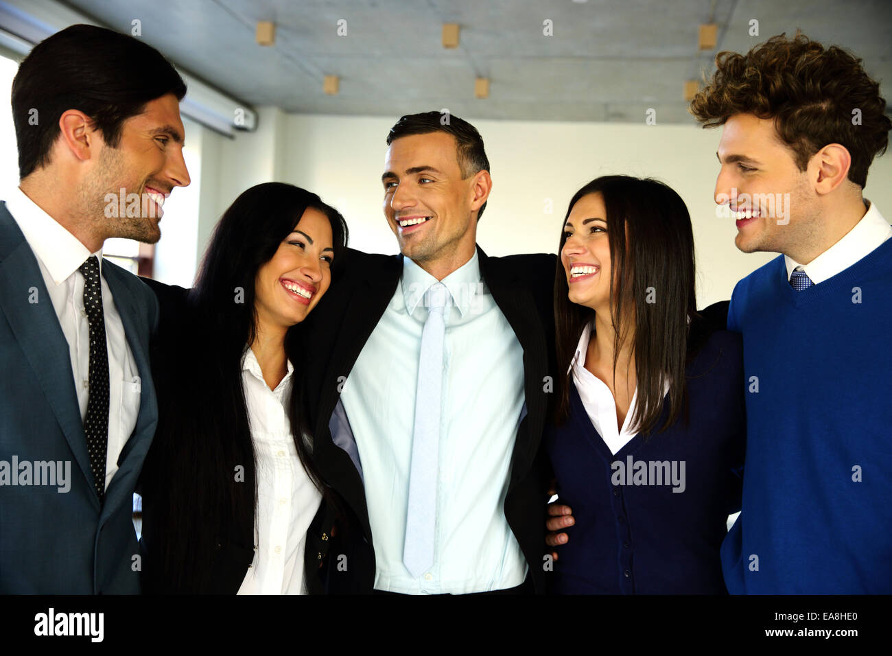Cheerful businesspeople standing in office and looking at each other Stock Photo