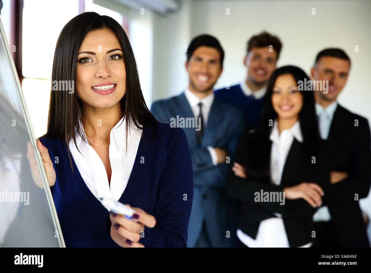 Smiling business team with flip board in office - Stock Image