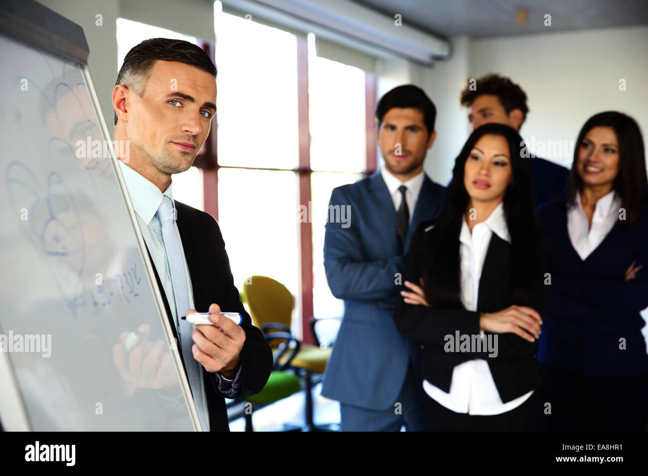 Businessman explaining something on the flipboard to his colleagues - Stock Image