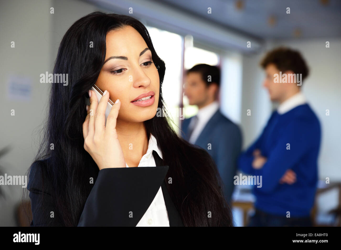 Serious businesswoman talking on the phone with colleagues on background - Stock Image