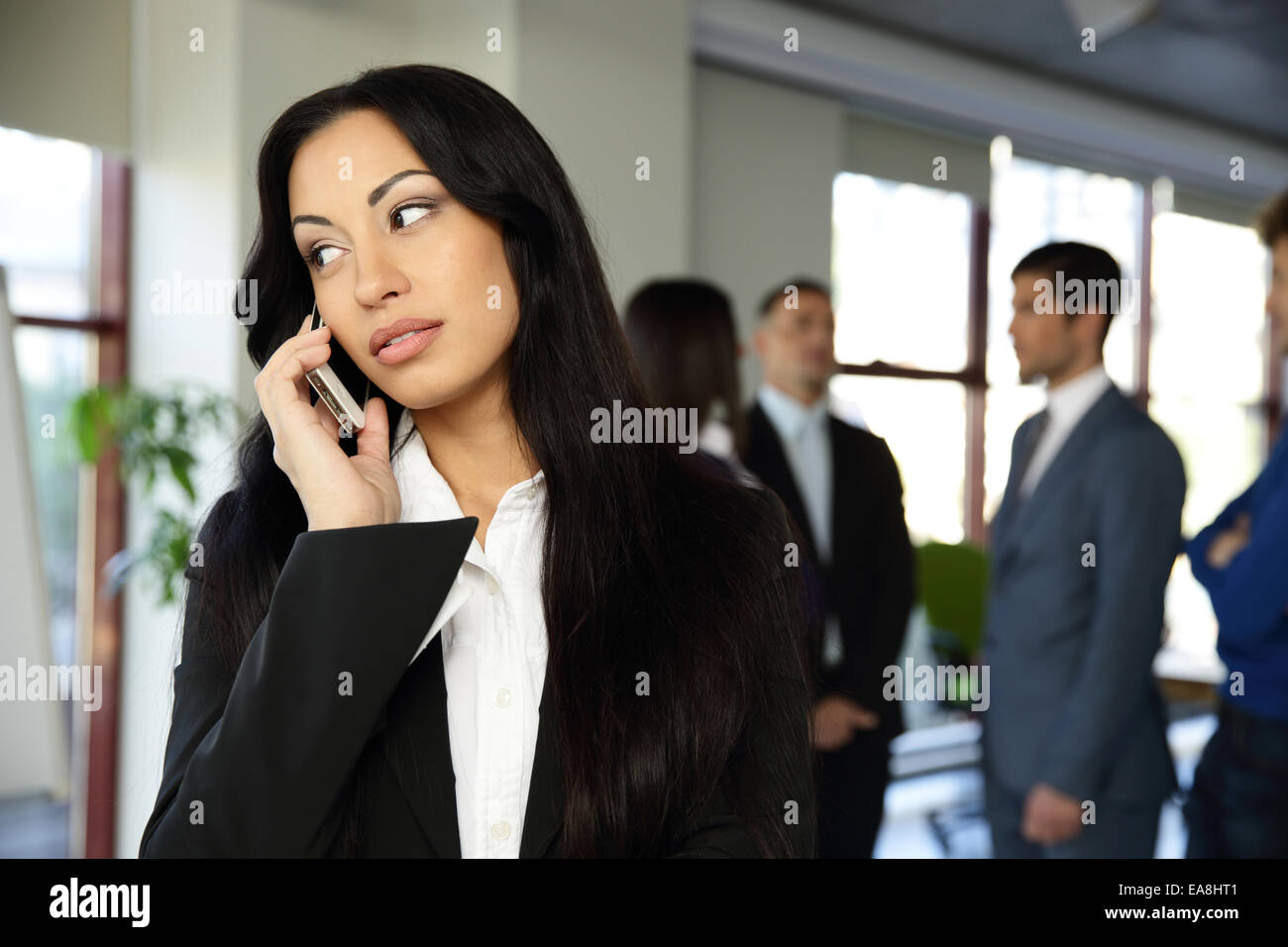 Beautiful businesswoman talking on the phone with colleagues on background - Stock Image