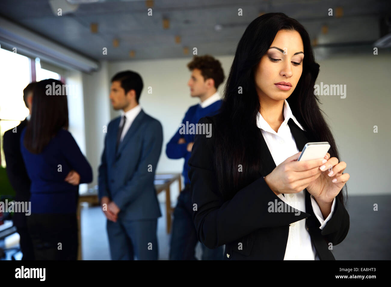 Beautiful woman using smartphone with colleagues on background - Stock Image