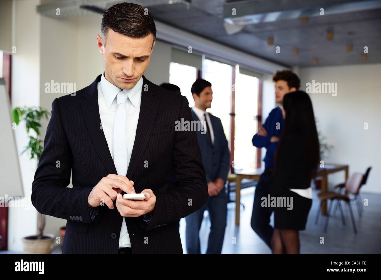 Confident businessman using smartphone in front of a colleagues - Stock Image