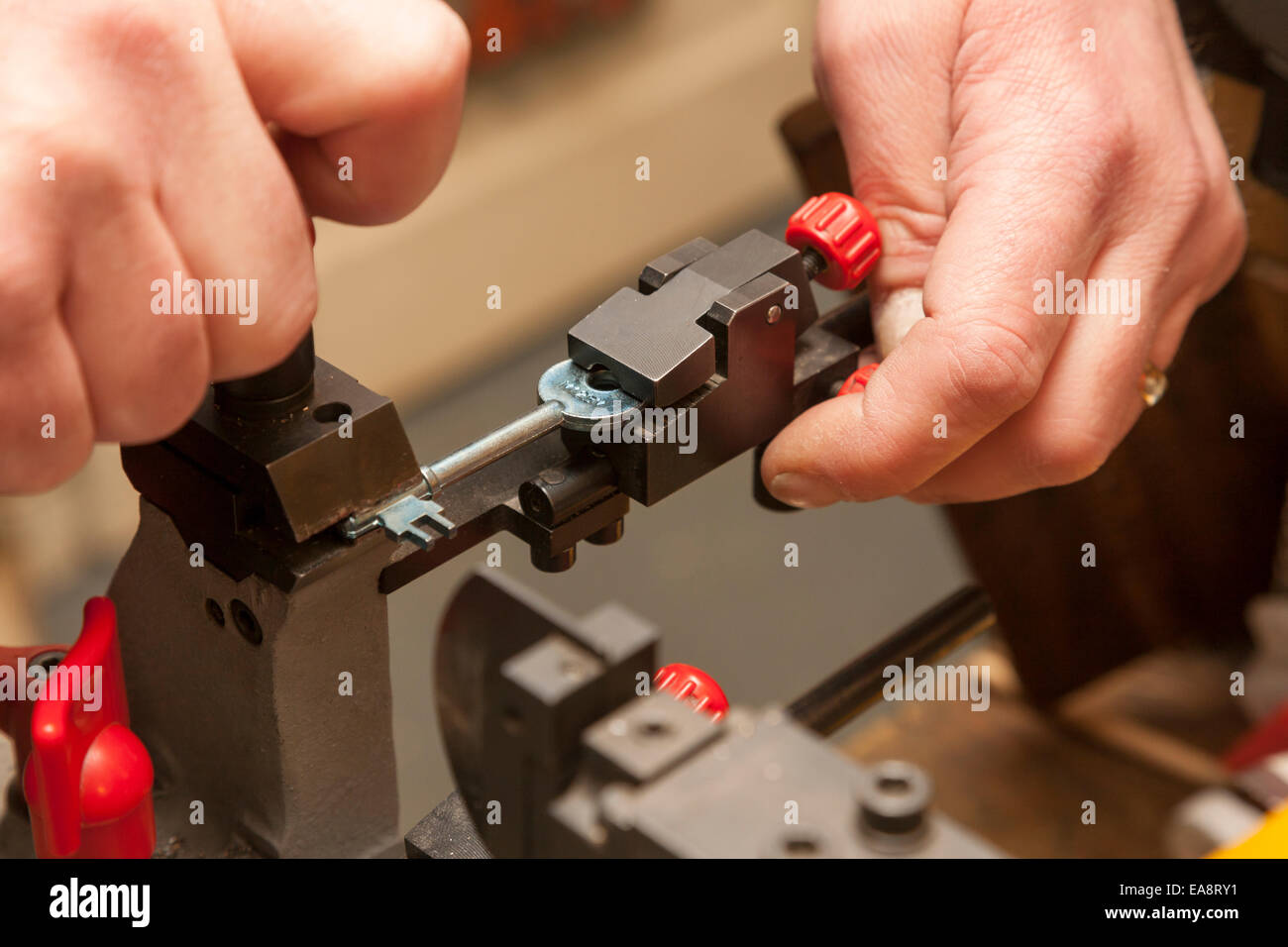 A locksmith cutting keys in a locksmith's shop - Stock Image