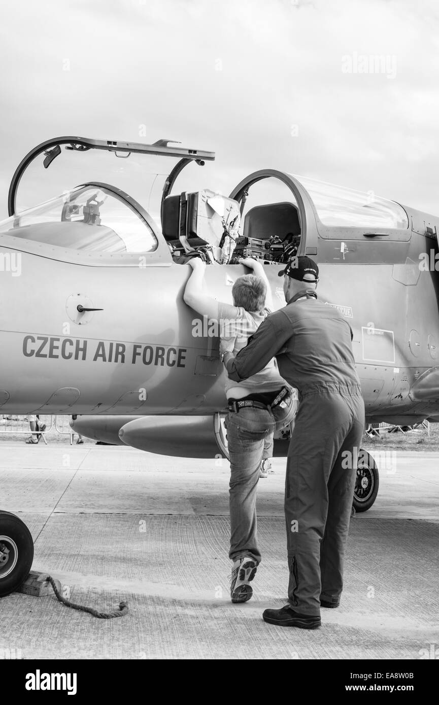 A young boy gets shown a Czech air force Aero L-159 Alca multi-role aircraft at the Malta International Airshow Stock Photo