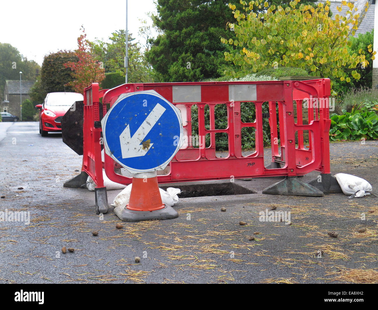 Roadworks with protective fencing around hole in road - Stock Image