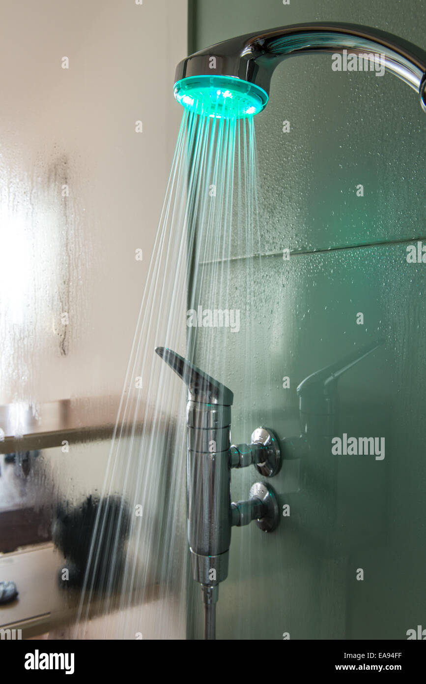Interior Of A Glass Shower Cabin With Running Water And Moisture On Head Has Colored Light