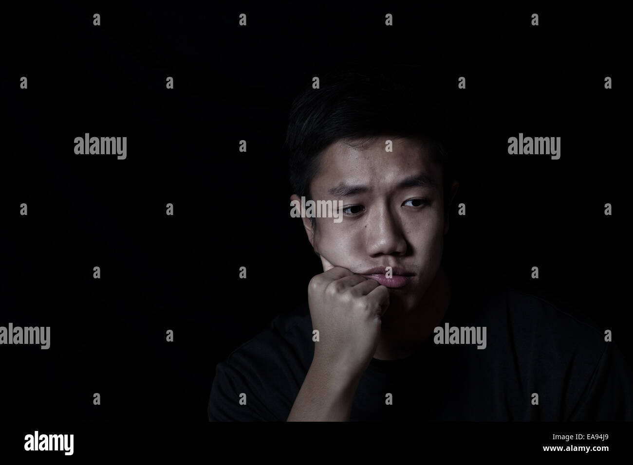 Young man depressed on black background - Stock Image