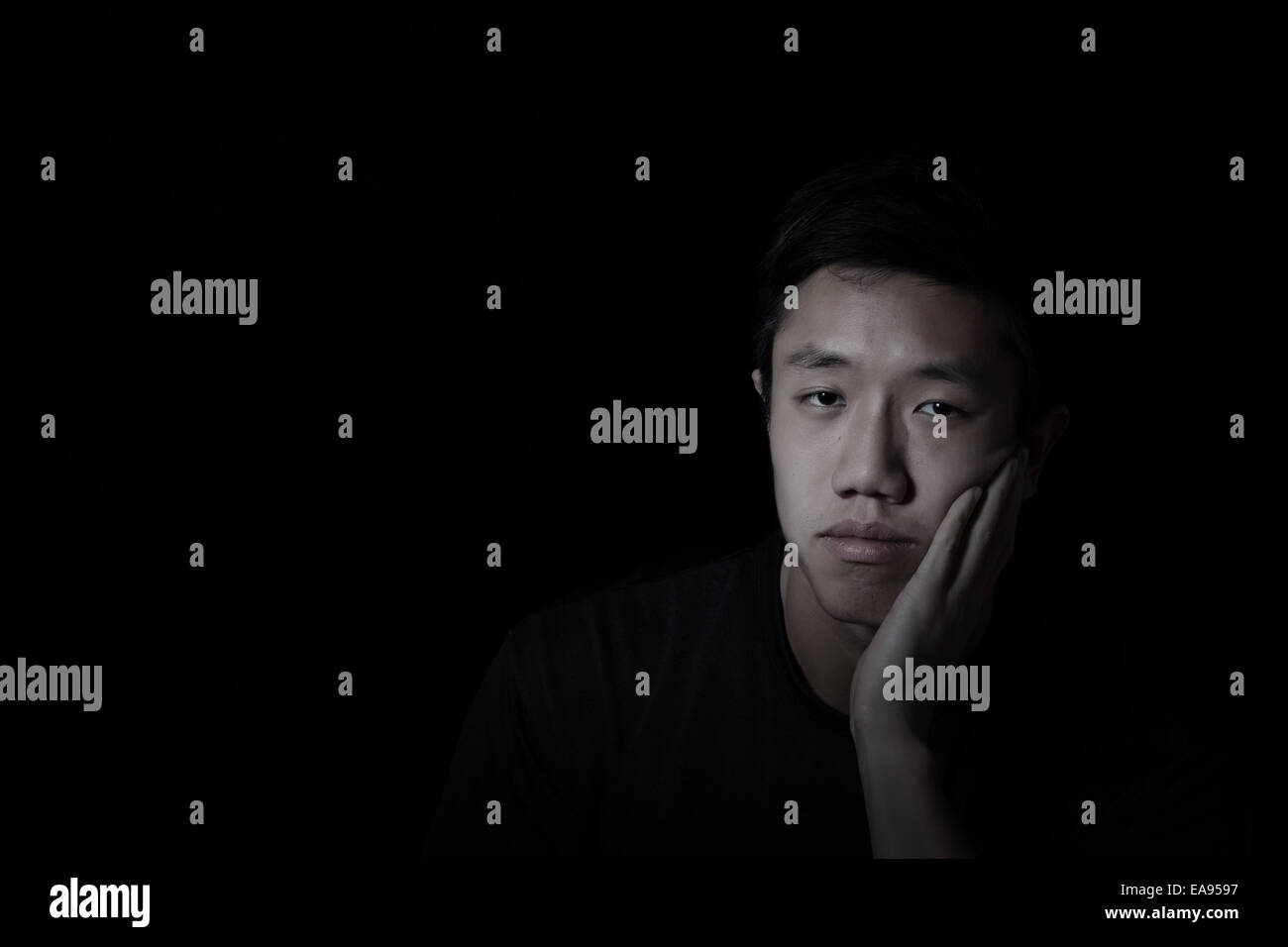 Young man, looking forward, showing depression with black background - Stock Image