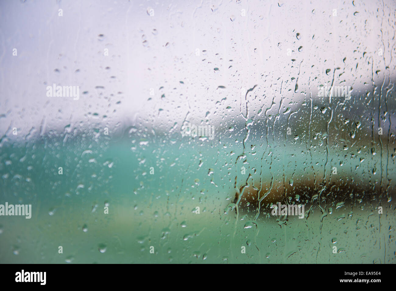 blurred view of the lake seen through a window with sharp drops on a rainy day - Stock Image
