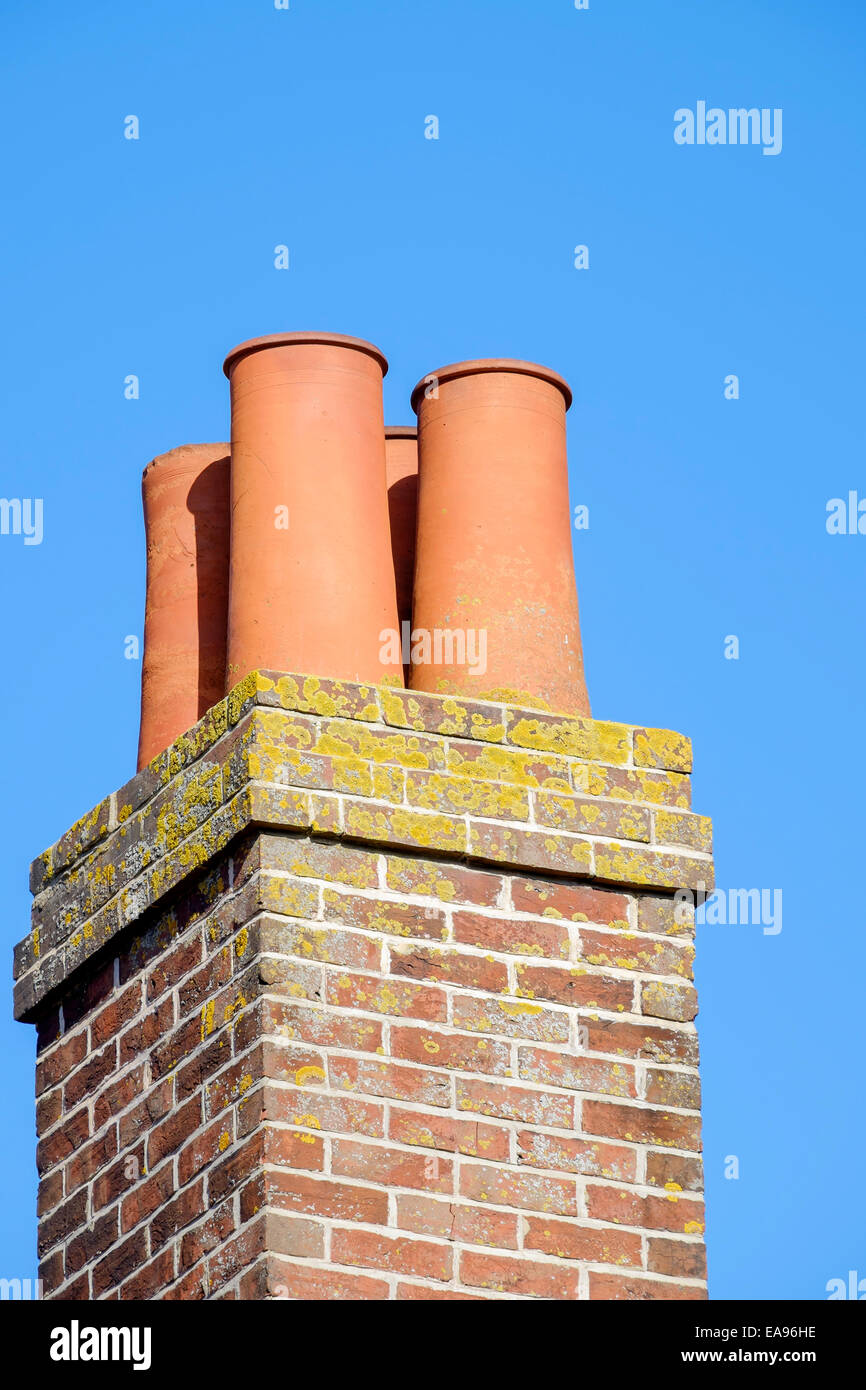 red terracotta clay chimney pots mounted on top of a red clay brick chimney stack shown against a blue sky - Stock Image