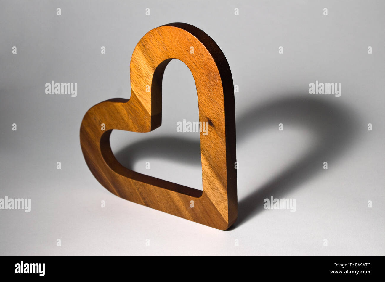Wooden heart with heart-shaped shadow giving appearance of two hearts. - Stock Image
