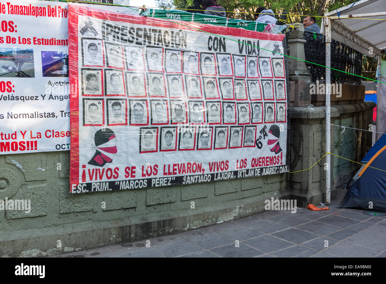 Banners demanding justice for the missing students believed executed by corrupt police hang from the main square - Stock Image