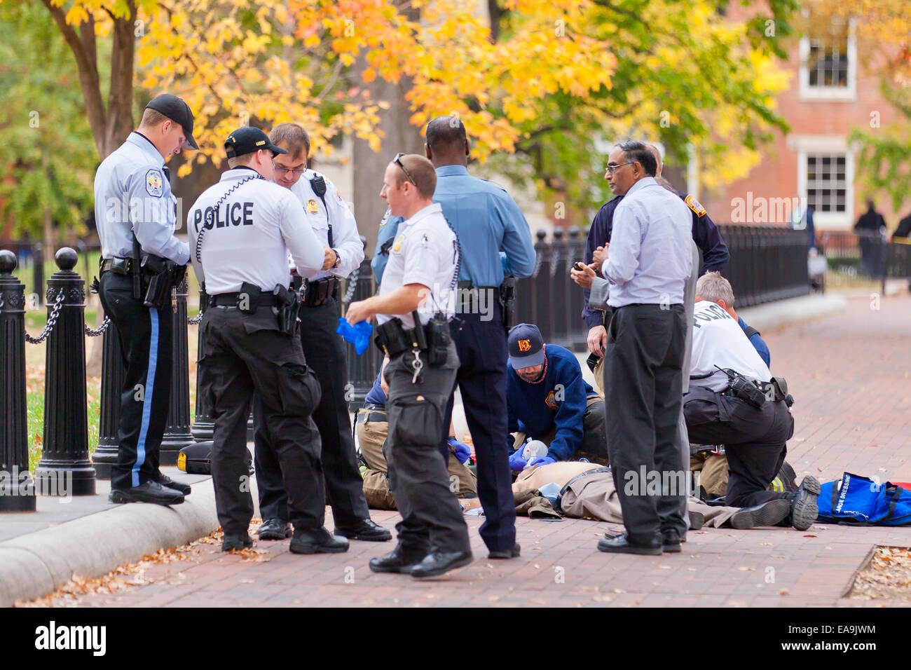 Police and EMS helping crime victim lying on ground - Washington, DC USA - Stock Image