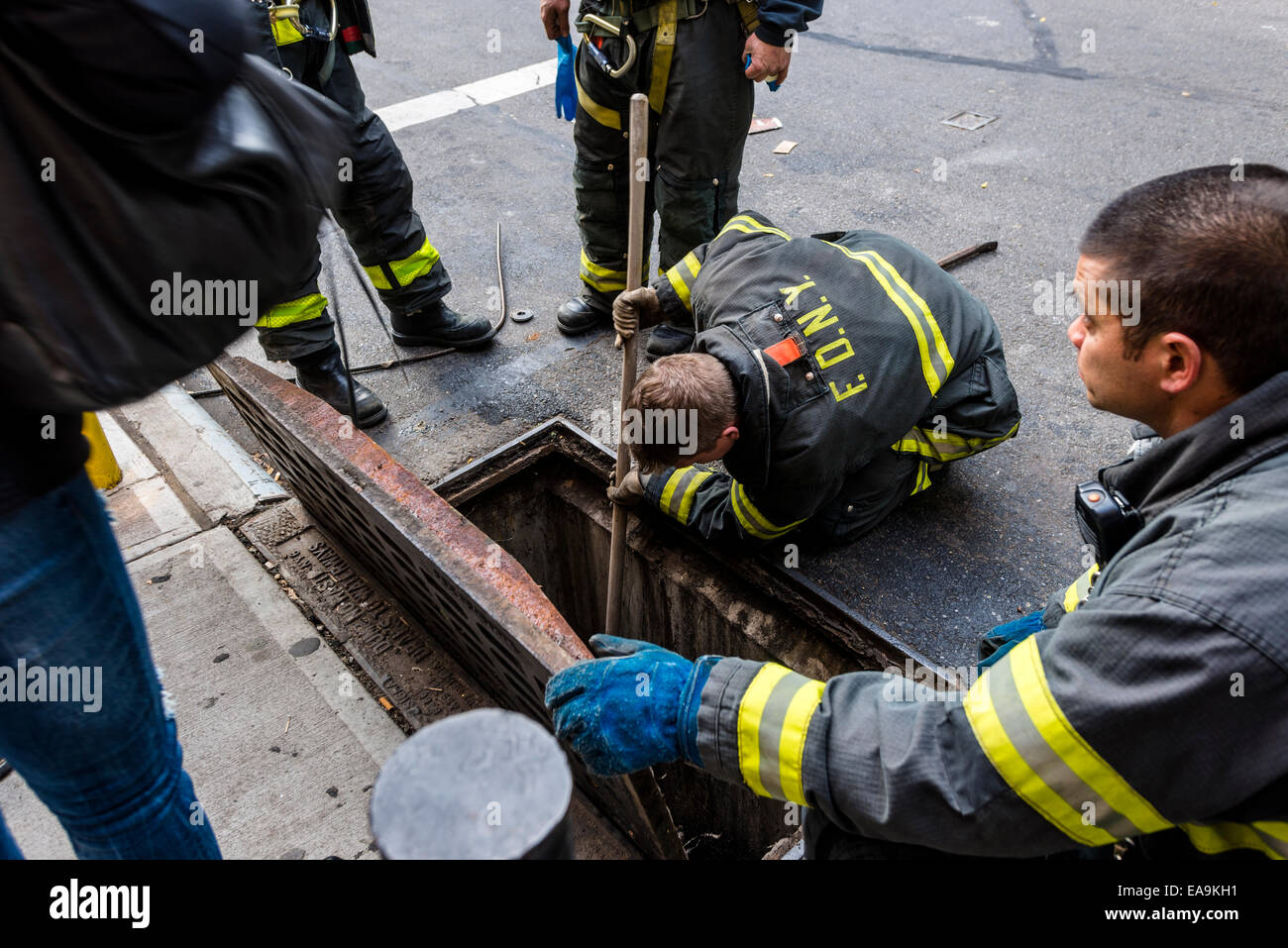 New York, NY 9 November 2014 - Fire fighters using tools to fetch lost keys that fell down a sewer. - Stock Image