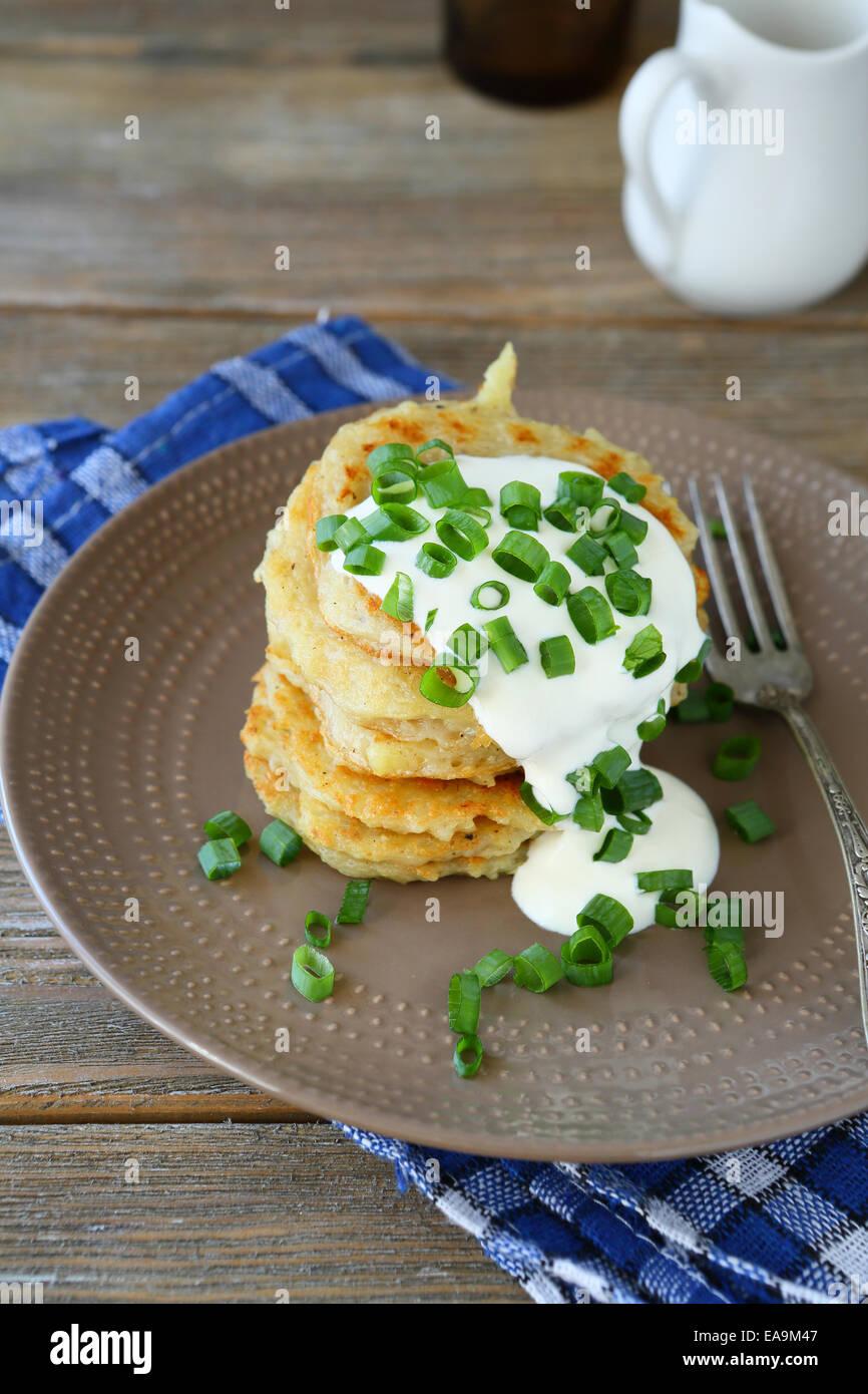 Fried potato pancakes with sour cream, food - Stock Image