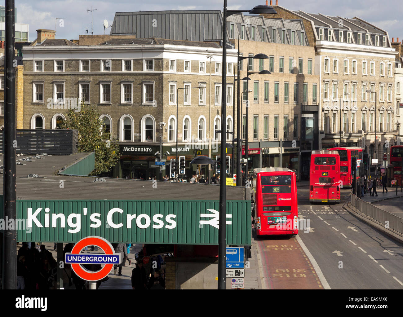 The scene outside the front of Kings Cross Station on the Euston Road; buses and fast food outlets. The Kings Cross - Stock Image
