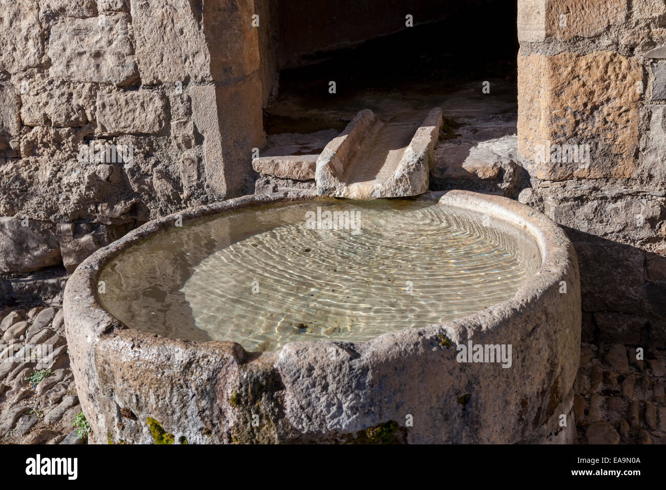 The original basin fountain of the Saint Cristofol church, in Peyre (Aveyron - France). Directly dug in the cliff, - Stock Image