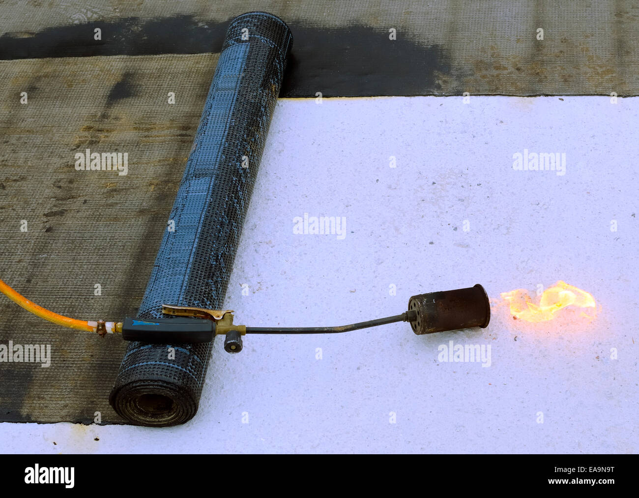 roofing felt roll and one torch blowpipes with open flame - Stock Image