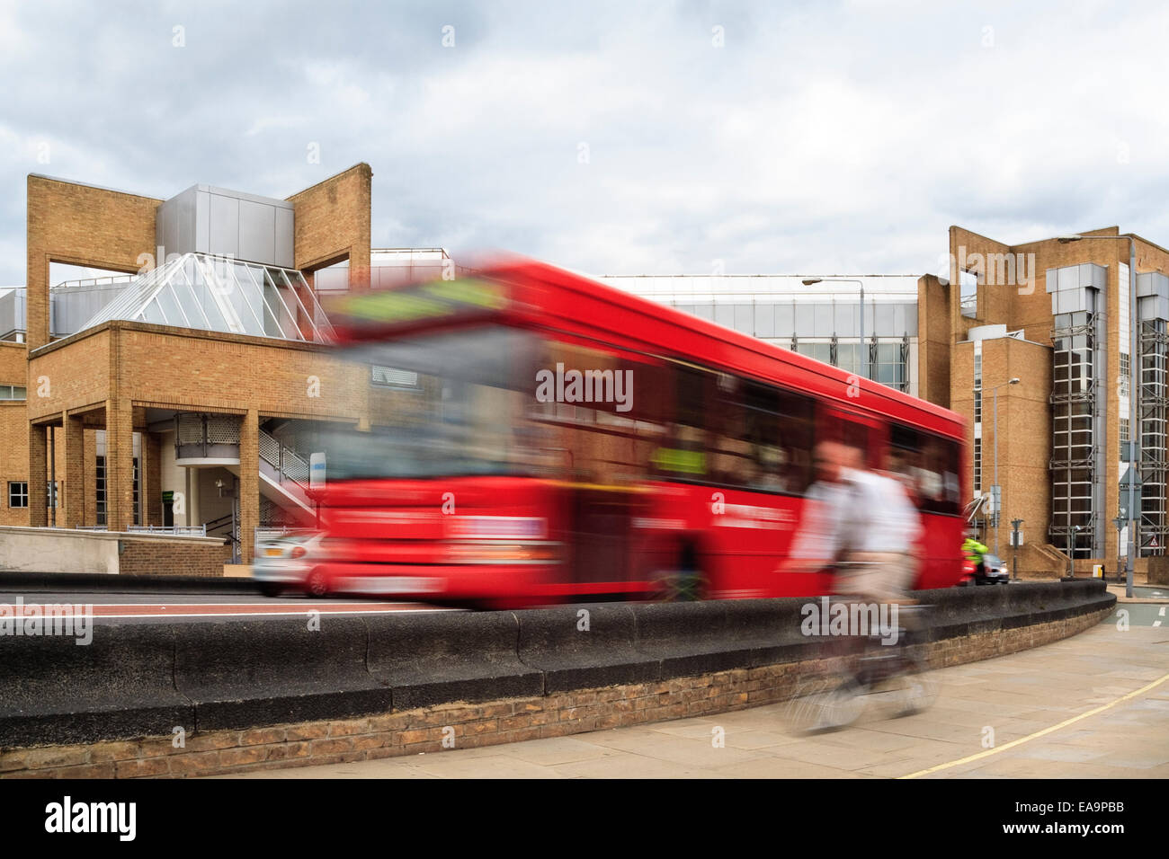 blurred motion image of cyclist and red bus in Kingston, London, UK - Cycle lane separated from traffic by a wall. - Stock Image