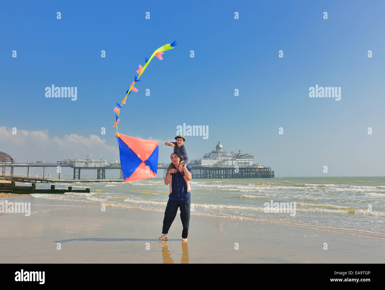 Grandfather with grandson flying a kite on the beach at Eastbourne. East Sussex. UK - Stock Image
