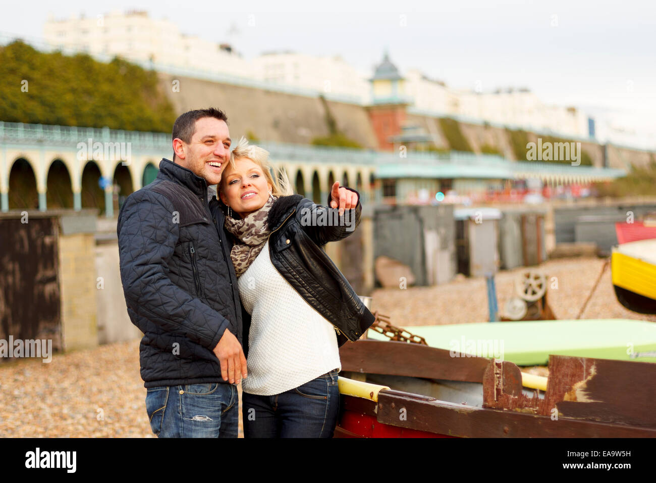 A couple enjoying a day out at the British seaside in Brighton in warm winter clothing Stock Photo