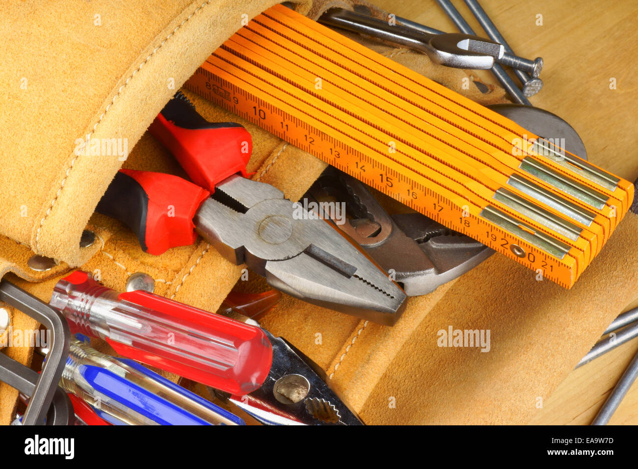 Close-up of a hand tool set with screwdrivers, hexagonal keys, a pair of pliers, a metric ruler and some other tools. - Stock Image