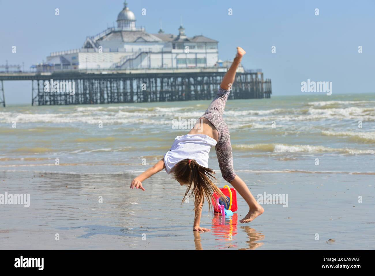 Girl performing a cartwheel on Eastbourne beach. East Sussex. - Stock Image
