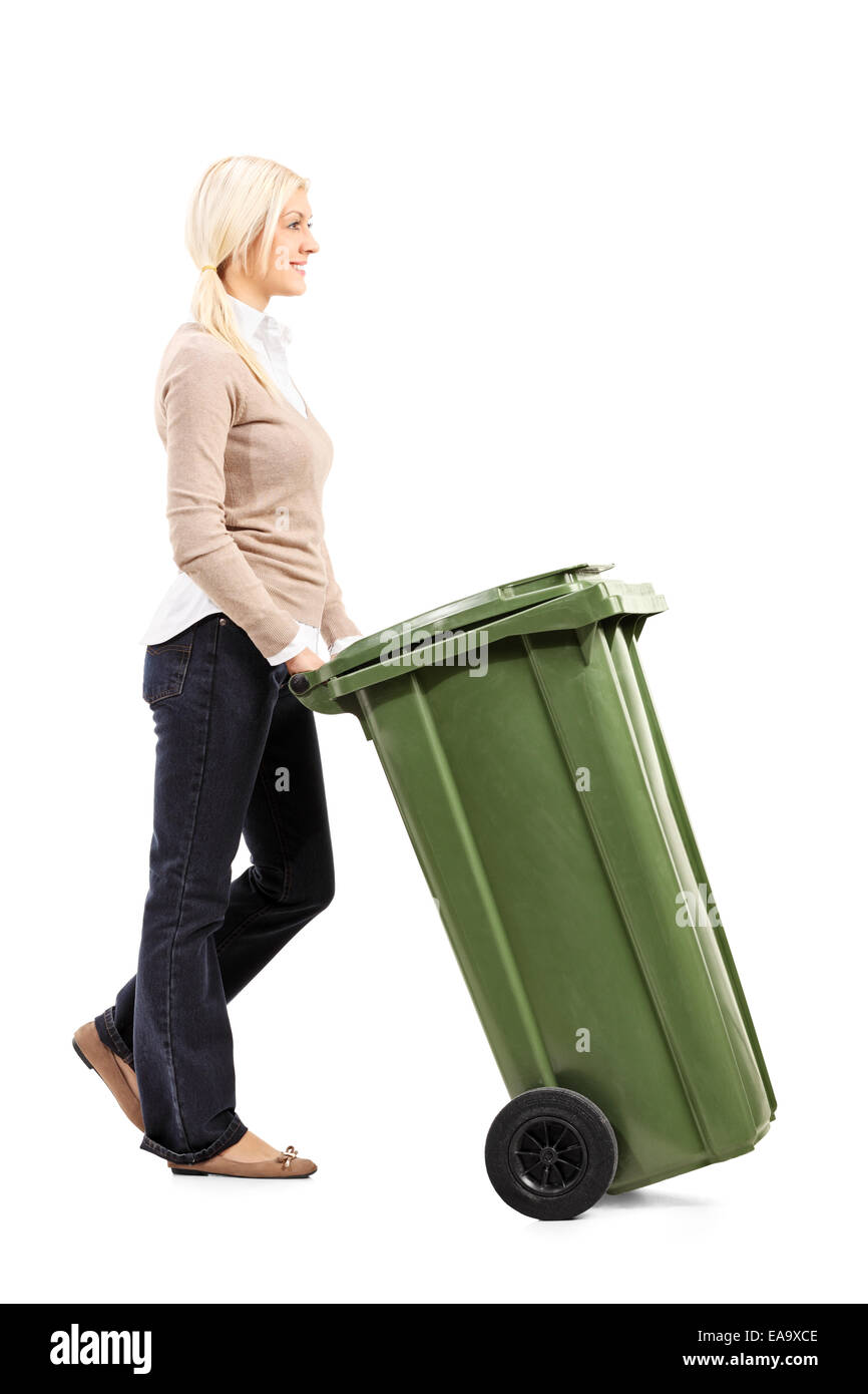 Cheerful young woman pushing a garbage can isolated on white background - Stock Image