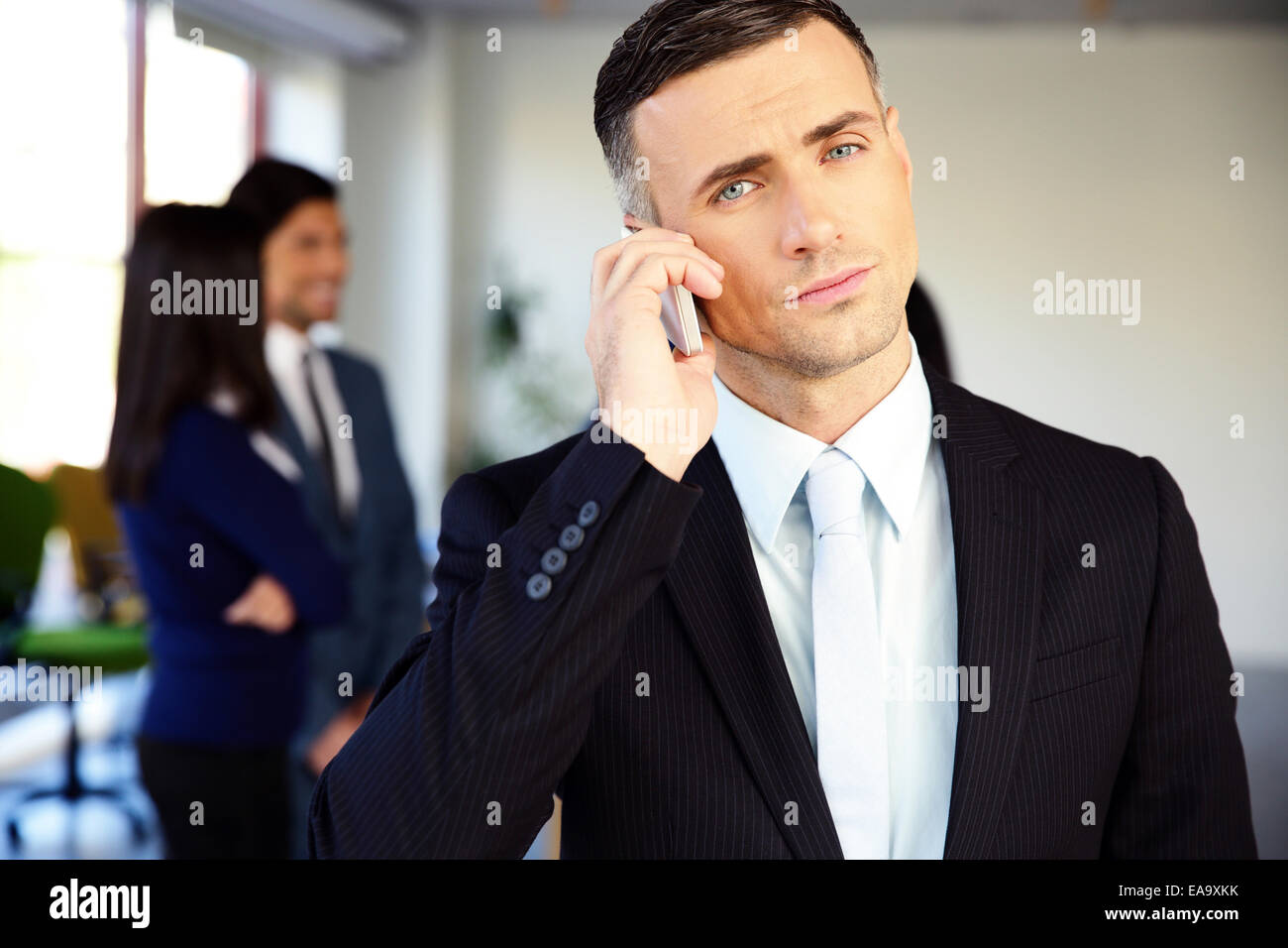 Confident businessman talking on the phone in office - Stock Image