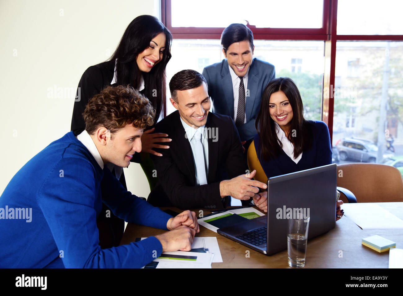 Happy businesspeople working in the office together - Stock Image
