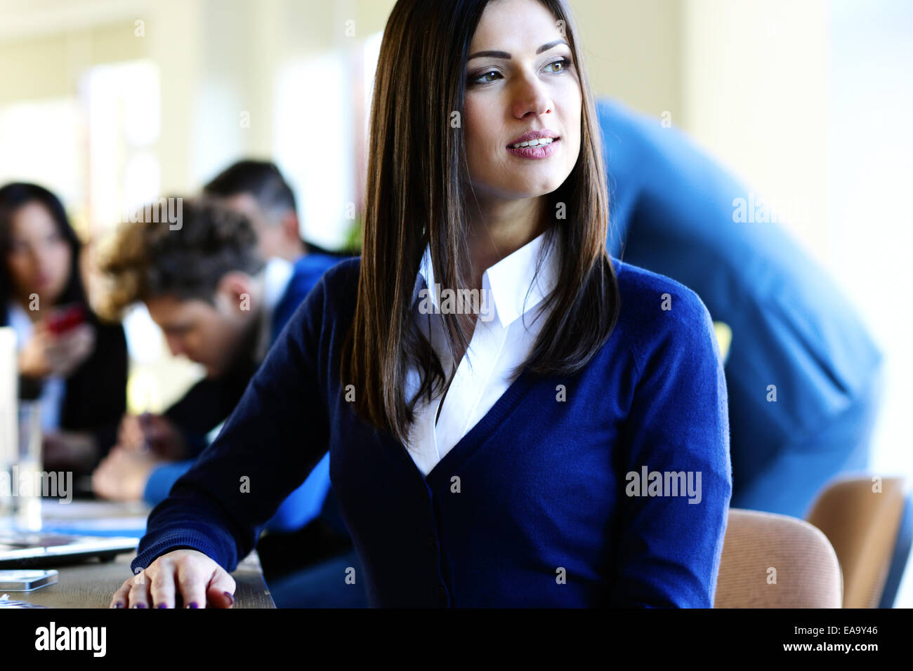 Pensive businesswoman sitting at the table with colleagues on background - Stock Image