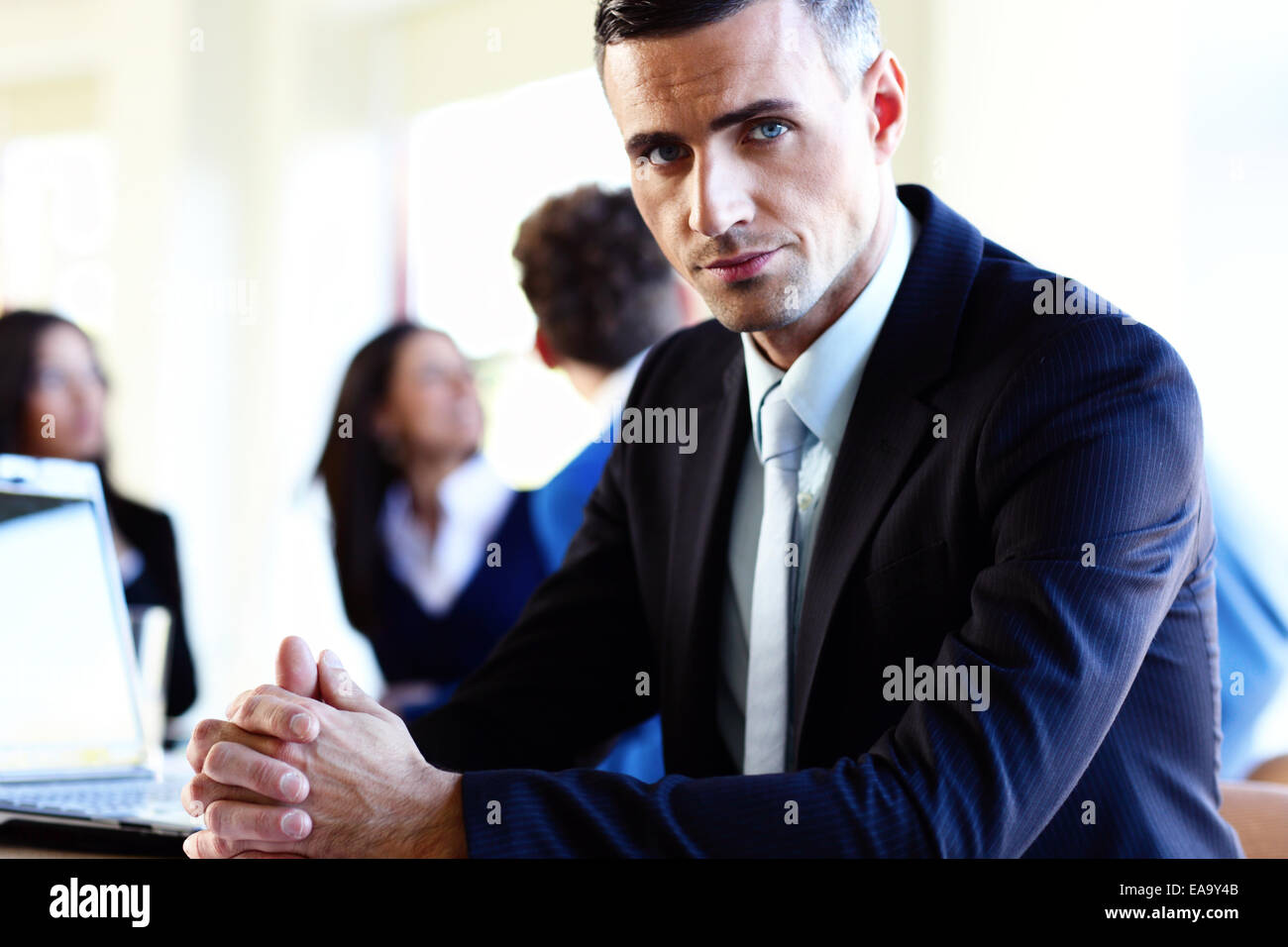 Serious businessman sitting at the table in front of colleagues - Stock Image