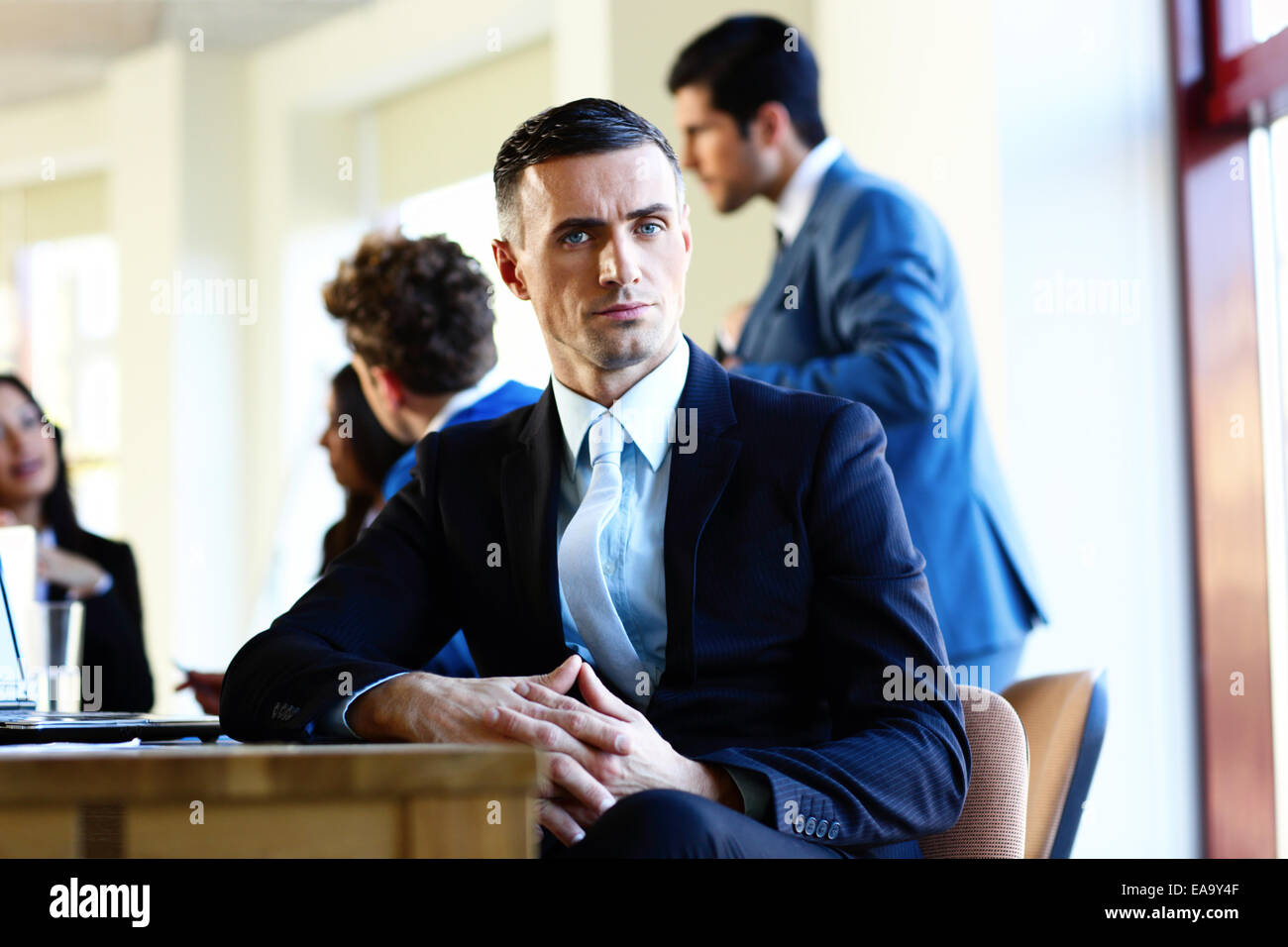 Confident businessman sitting at the table with colleagues on background - Stock Image