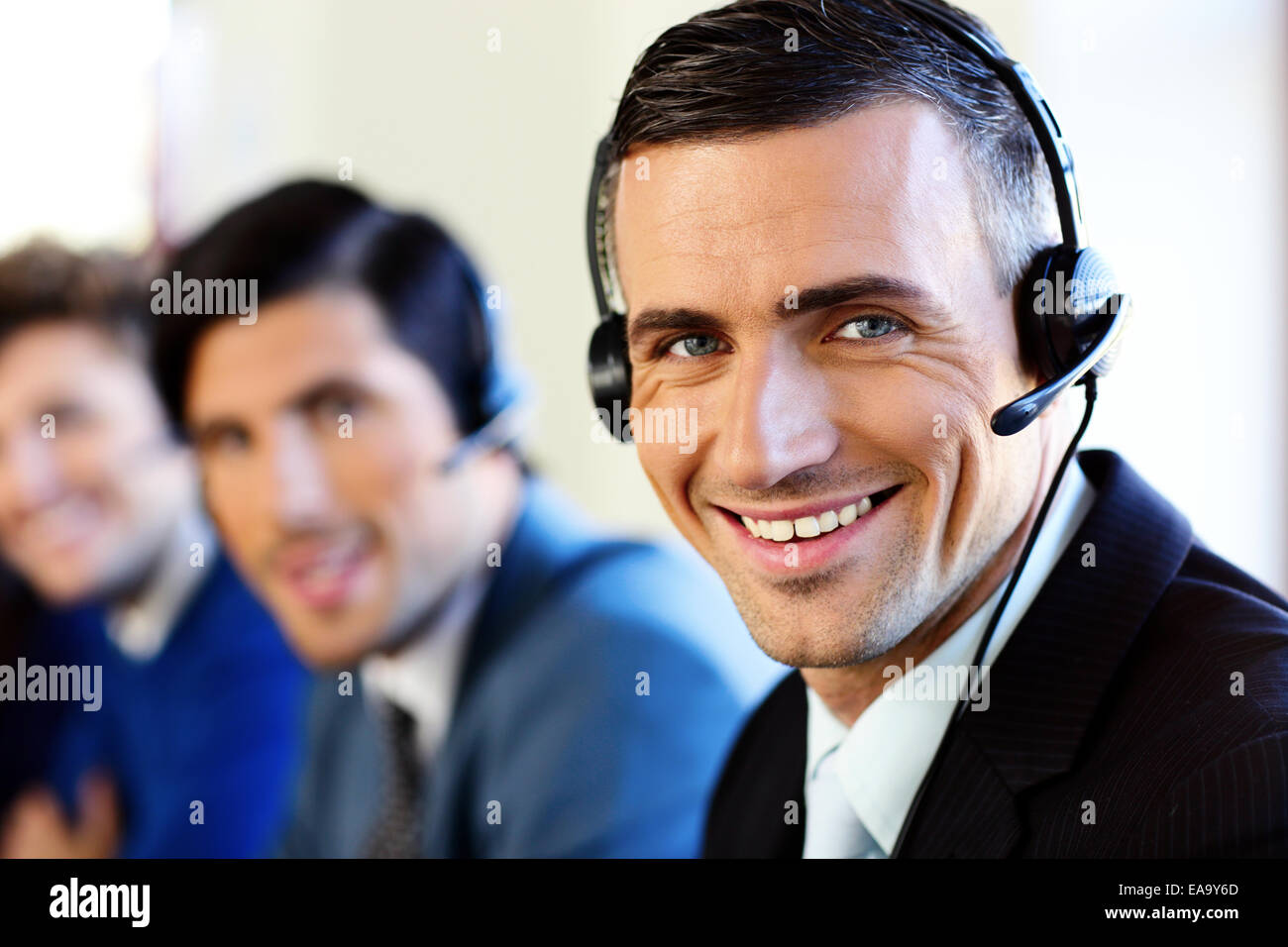 Smiling young businesspeople and colleagues in a call center office - Stock Image