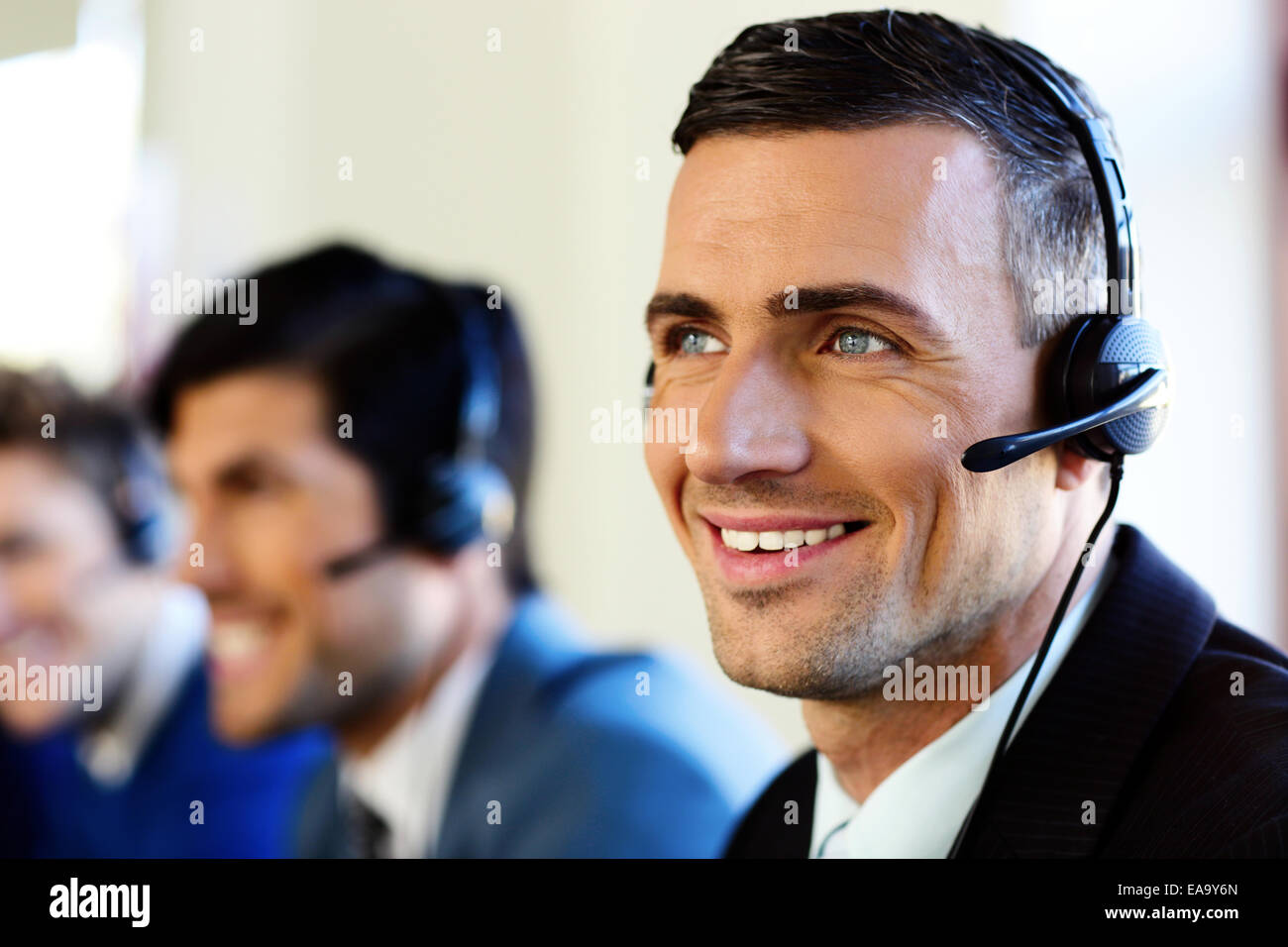 Attractive positive young businesspeople and colleagues in a call center office - Stock Image