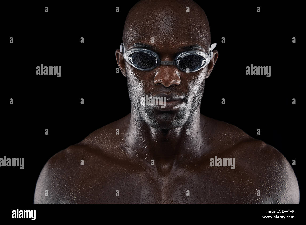 Portrait of confident male swimmer looking at camera against black background. Close-up image of muscular young - Stock Image