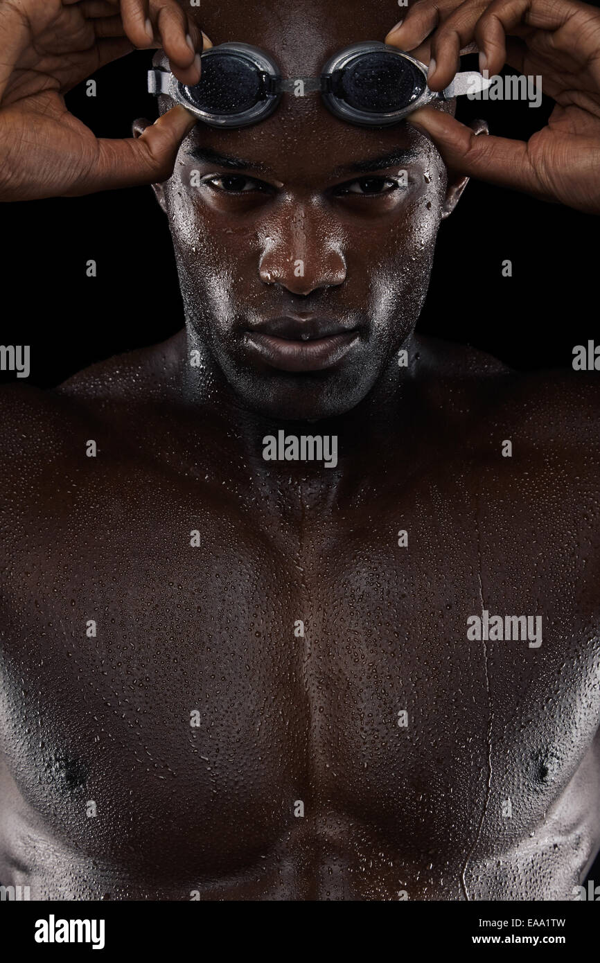 Close-up shot of determined male swimmer with goggles looking at camera. Young african man with wet body. - Stock Image