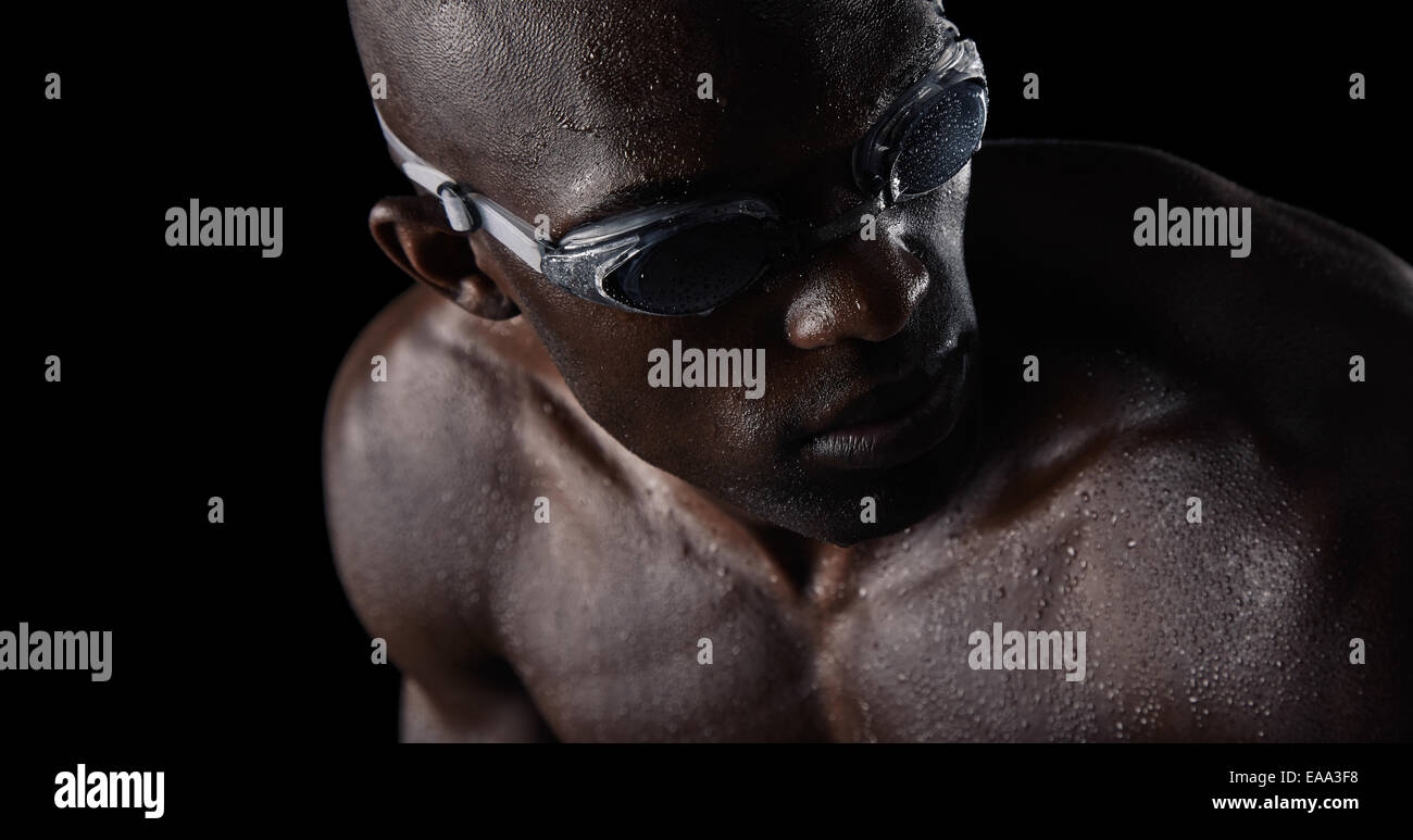 Close-up image of African male athlete with swimming goggles looking over shoulder. Professional swimmer on black - Stock Image