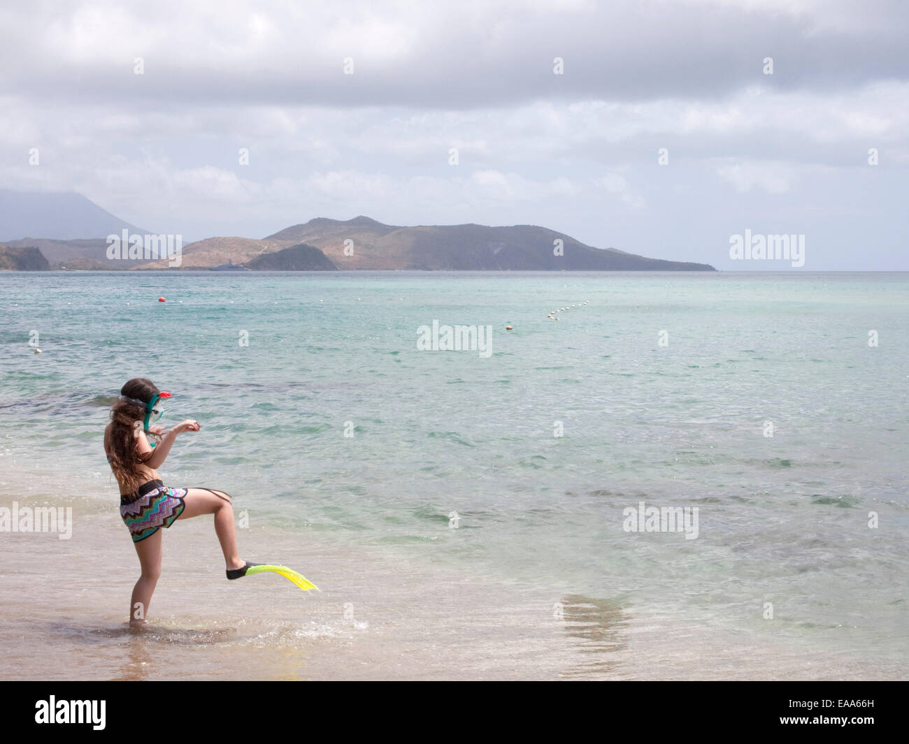 girl in snorkel gear walks towards sea - Stock Image
