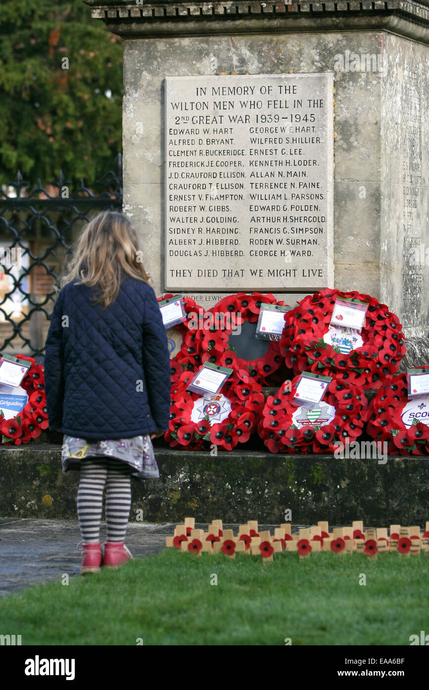 Wilton, Wiltshire, UK. 09th Nov, 2014. A young girl pays her respects after a Remembrance Day service at the church - Stock Image